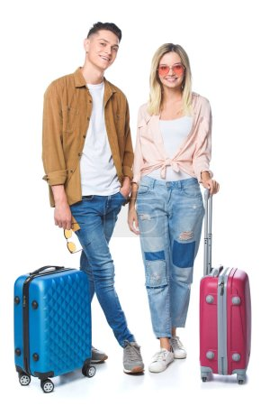 young travelling couple with suitcases looking at camera isolated on white