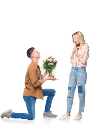 side view of happy young man making proposal to girlfriend isolated on white