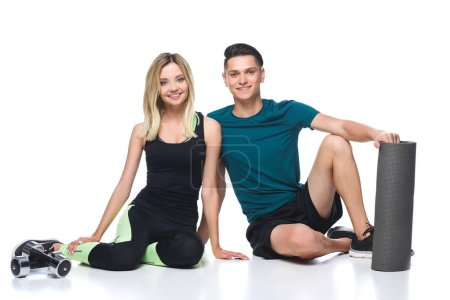 fit young couple in sportswear sitting on floor isolated on white