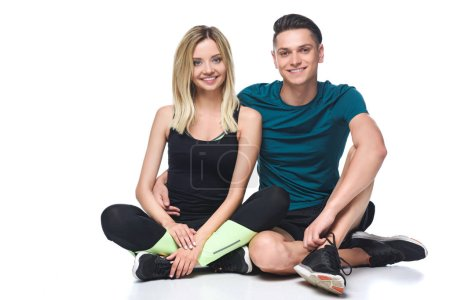 sporty young couple in sportswear sitting on floor isolated on white