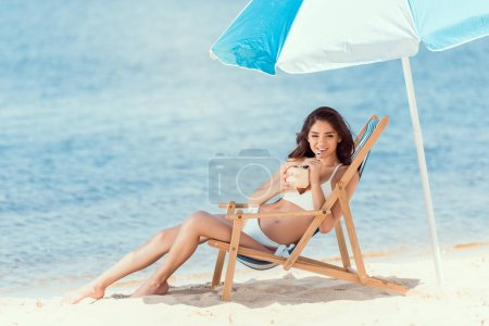 happy young woman drinking cocktail in deck chair under sun umbrella near sea