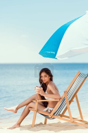 young woman drinking cocktail in beach chaise longue under sun umbrella