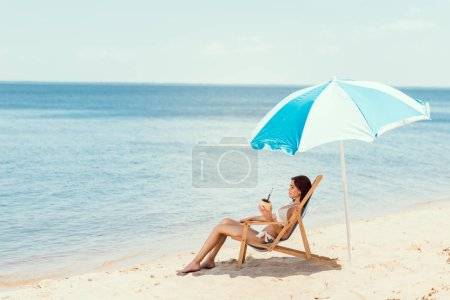 beautiful girl in bikini with coconut cocktail resting on deck chair under beach umbrella near sea