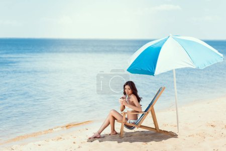 young woman in bikini drinking coconut cocktail in beach chaise longue under sun umbrella near sea