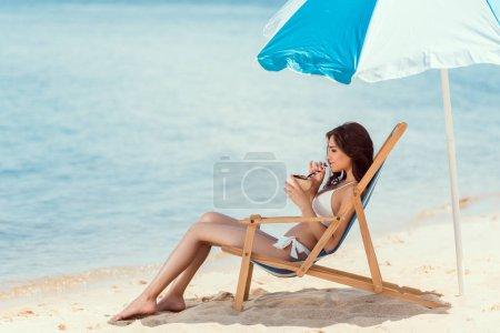 attractive girl in bikini drinking coconut cocktail in beach chair under umbrella