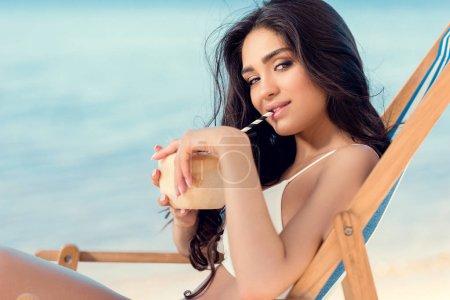 beautiful girl in bikini drinking coconut cocktail and sitting in beach chair