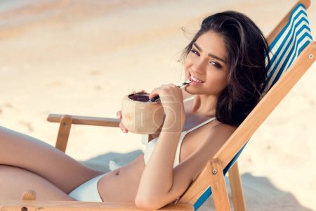 Photo for Beautiful girl in bikini drinking coconut cocktail on beach - Royalty Free Image