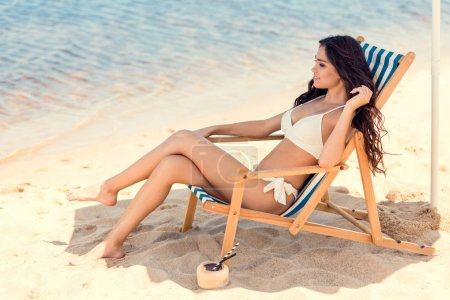 beautiful girl in bikini sitting on beach chair with coconut cocktail on sand
