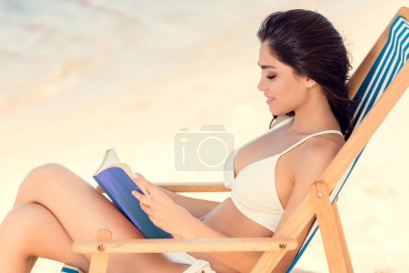 attractive brunette woman reading book on beach chair
