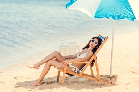 woman in sunglasses and bikini relaxing on beach chair under umbrella near the sea