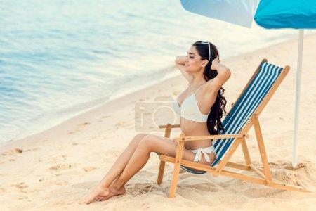 attractive girl sitting on beach chair under umbrella near the sea