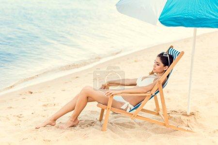 attractive brunette girl relaxing on beach chair under umbrella near the sea