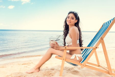 young woman in bikini drinking coconut cocktail while relaxing on deck chair