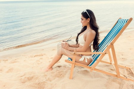beautiful young woman with green coconut drink on sandy beach