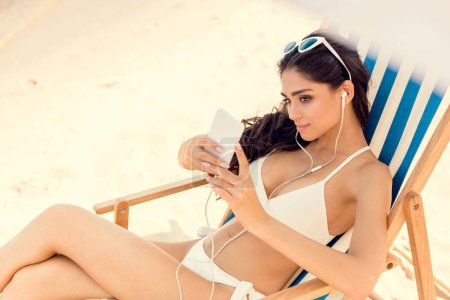 Photo for Attractive woman taking selfie on smartphone while relaxing on beach chair - Royalty Free Image
