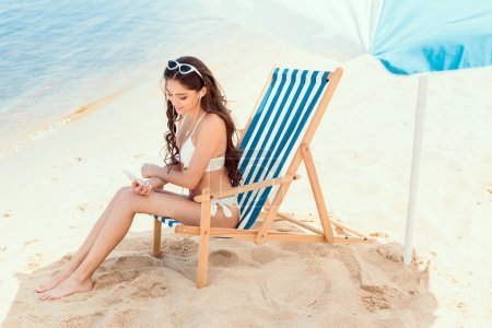 attractive woman using smartphone and resting on beach chair under sun umbrella near sea on resort