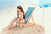 attractive woman using smartphone and resting on beach chair under sun umbrella near sea on resort
