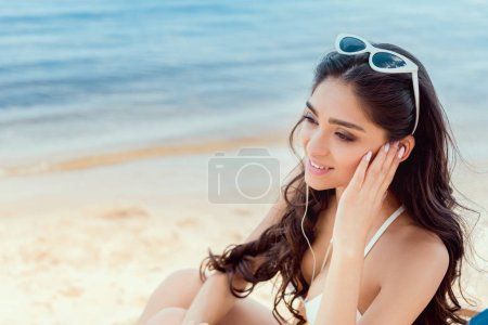 attractive girl listening music with earphones near sea on resort