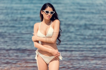 slim brunette woman posing in sunglasses and white swimsuit near the sea