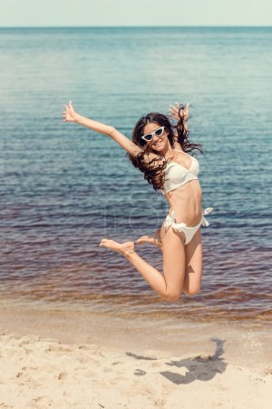 excited woman in sunglasses and white bikini jumping on beach near the sea