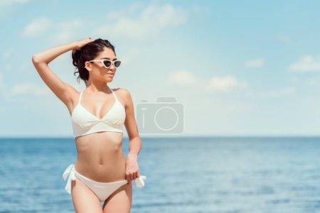 Foto de Mujer joven atractiva posando en gafas de sol y traje de baño blanco cerca del mar en el resort - Imagen libre de derechos