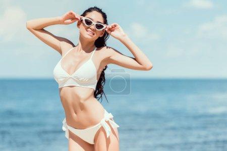 happy slim young woman posing in sunglasses and white bikini near the sea on resort
