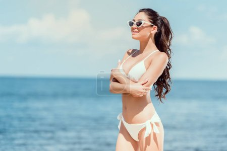 beautiful girl posing in sunglasses and bikini near the sea on resort