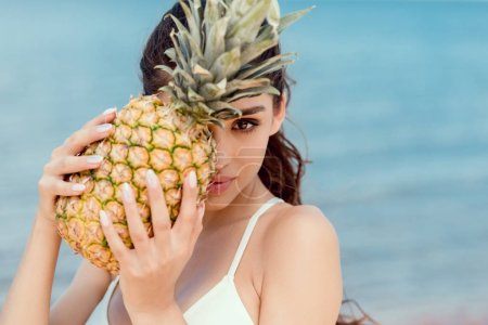 portrait of attractive girl in bikini holding fresh pineapple near the sea