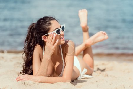 attractive young woman in sunglasses and bikini relaxing on beach at sea