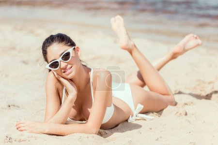brunette woman in sunglasses and bikini relaxing on beach at sea