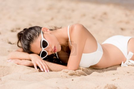 attractive girl in sunglasses and white bikini lying on sand