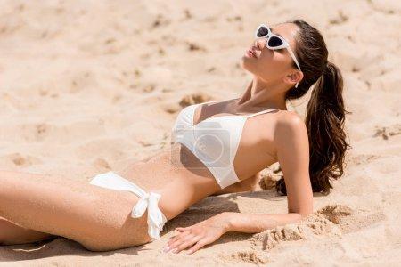 beautiful slim girl in sunglasses and white bikini sunbathing on sand