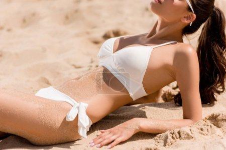 cropped view of sexy slim girl in white bikini lying on sand