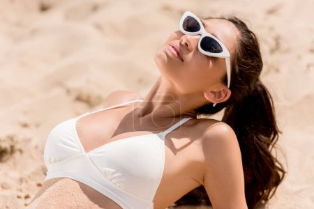 brunette woman in sunglasses and white bikini sunbathing on sand