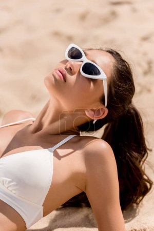 beautiful young woman in sunglasses and white bikini sunbathing on sand