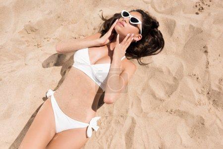 Photo pour Vue de dessus d'une fille séduisante en lunettes de soleil et bikini blanc bronzer sur le sable - image libre de droit