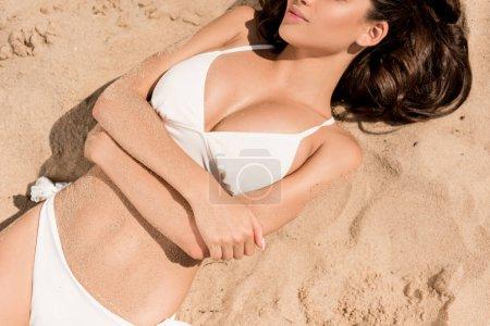 cropped view of slim girl in white bikini lying on sandy beach