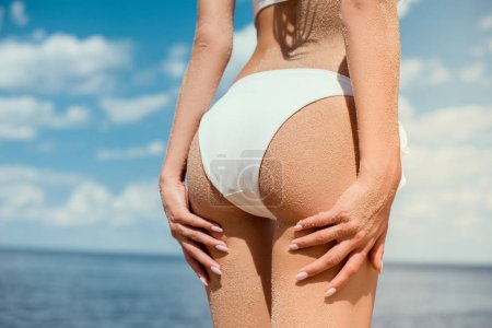 cropped view of girls buttocks in white bikini near the sea