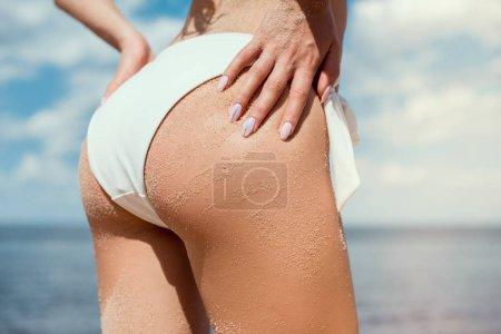 cropped view of girls buttocks in white bikini