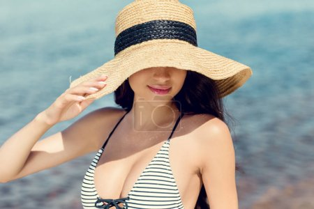 attractive girl posing in swimsuit and straw hat near the sea