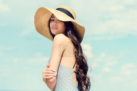 attractive brunette girl posing in straw hat