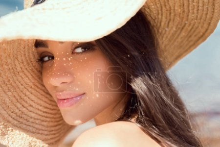 portrait of attractive girl posing in straw hat