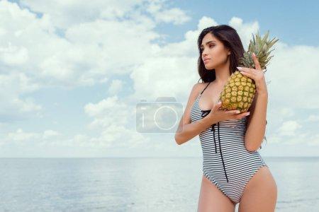 beautiful woman in swimsuit posing with pineapple near the sea