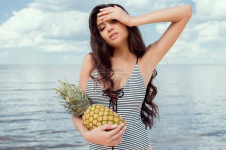 attractive brunette woman in swimsuit posing with pineapple near the sea