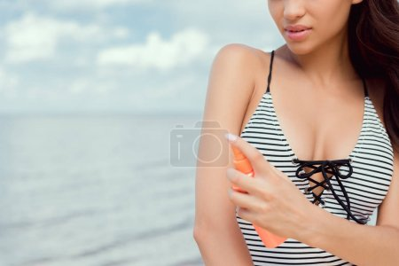 cropped view of young woman in swimsuit applying sunscreen on body