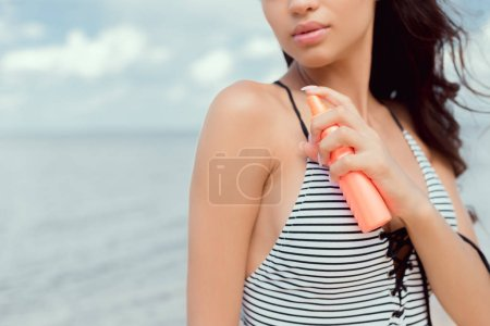 cropped view of girl in swimsuit applying sunscreen on body