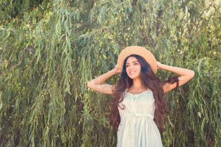 smiling brunette girl in straw hat and white dress posing near willow tree
