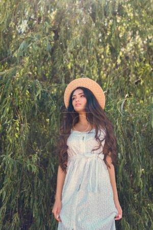 belle fille en chapeau de paille et robe blanche posant près de saule arbre