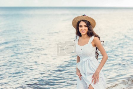 smiling woman in straw hat and white dress walking near the sea