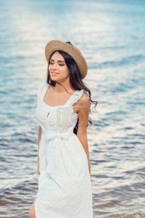 beautiful happy girl in straw hat and white dress walking near the sea